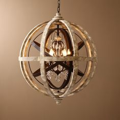 Bold and unique, this 4-light chandelier combines weathered wood, metal in rust, and crystals for a perfect mix of rustic and industrial styles. A pristine wooden globe encasing a metal orb in rust ho