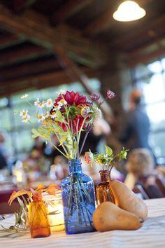 vintage glass bottles, wildflowers, rustic pears; wedding table centerpiece