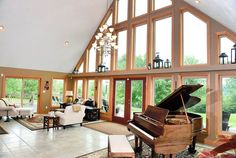 Living room with wall of large windows, multi-level chandelier, piano and tile floor.