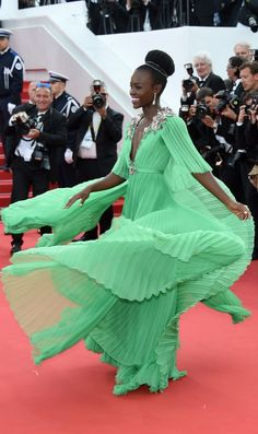 Lupita Nyong'o wearing a custom green Gucci gown complete with floral appliqué and chiffon pleating. She accessorized her look with glowing Chopard jewels at Cannes Film Festival 2015.