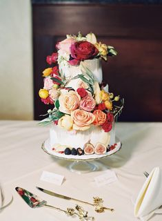 white and gold tiered wedding cake adorned with florals and fruit | Photography: Michael & Carina