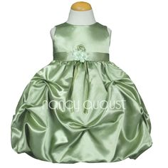 Sage Baby Dress with Pick Up Skirt: This immaculate green sage baby dress is ideal if you are going for a classically, beautiful look. A sleeveless bodice made of shiny satin is matched with a lovely satin skirt. The voluminous skirt features dainty little pick-ups and gathers; a fresh, new take on a skirt design! This amazing shiny sage baby dress is finished with a sewn in waist sash that is adorned with a lovely, detachable flower pin complete with flowing ribbons.