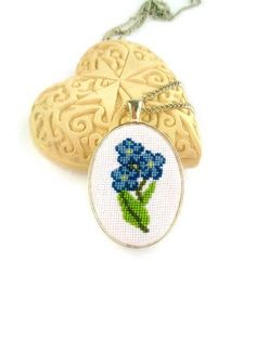 Fresh and tender flower jewelry with accurate hand embroidery will complete cute feminine outfit. This cross stitched necklace designed with forget me not flowers looks great and adds nature beauty to your apparel. Hand embroidered jewelry is new world trend. It looks stylish and totally unique. This embroidery art contains very small crosses, that means long accurate hand needlework. Size of necklace is 1.5 inches x 1.18 inches (4 cm x 3 cm). Chain length is 18 inches (47 cm).