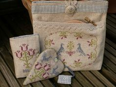 cross stitch used to decorate holders for sewing supplies