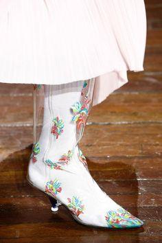 Weiße Stiefel mit floralem Motiv.