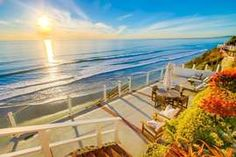 Sunset Beach | Encinitas | San Diego Vacation Home Rental | Enjoy a glass of wine watching breathtaking sunsets and whitewater ocean views from the comfort of your own home!  This newly remodeled 2 bedroom + 2 bathroom Ocean Front house features an amazing 55 feet of exclusive unobstructed Ocean Frontage, dual Ocean Front patios + a 3rd  East-facing patio that's ideal for enjoying sunrises, as well as private stairs that lead directly from our patio to a secluded stretch of white sandy…