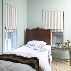 A sea-green guest bedroom with striped Roman shades, designed by Michelle Smith. | Lonny.com