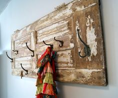 This is a great idea to turn an old door into a great rustic coat rack with vintage style hooks.