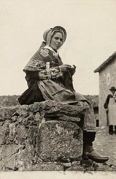 A young woman of Auvergne sits on a stone ledge and knits, 1921.