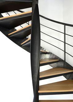 Photo DH109 - SPIR'DÉCO® Flamme Mixte. Escalier d'intérieur métallique design sur flamme centrale formant escalier hélicoïdal sans mât central avec volée droite à l'arrivée. Escalier contemporain en métal et bois installé dans un appartement en duplex. Option rampe s'arrêtant sous plafond + Option volée droite à l'arrivée. Finition : acier brut patiné naturelle. - © Photo : Léo DELAFONTAINE