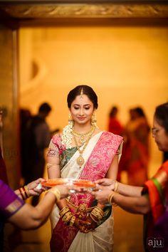 South Indian bride. Gold Indian bridal jewelry.Temple jewelry. Jhumkis. White and pink silk kanchipuram sari.braid with fresh jasmine flowers. Tamil bride. Telugu bride. Kannada bride. Hindu bride. Malayalee bride.Kerala bride.South Indian wedding.