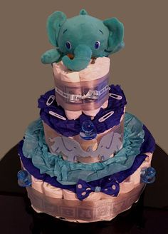 """- Three tier pampers diaper """"cake"""" - Decorated with tissue paper, baby ribbon, binki and clothespin props - Elephant felt cut outs and stuffed animal and a fabric bowtie on the bottom - Custom orders"""