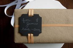 chalkboard gift tags - you could do this with black cardstock, or any card; also i love the way the ribbon threads over and under and over again.