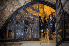 Snow starts to fall as religious men pray under enclosed archway at the western wall.