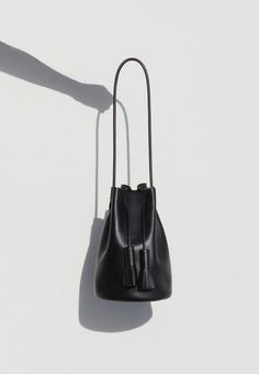 Building Block Smooth Leather Bucket Bag - Black - Rubber shoulder strap - Leather tassels - Leather lined base - Bag measured by strap measures - Made in the USA Building Block Bag, Fashion Still Life, Photography Bags, Product Photography, Black Leather Bags, Handbags On Sale, Smooth Leather, Evening Bags, Fashion Bags
