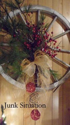 Old Wood Wagon Wheel...with pines & berries tied on with ribbon & ball ornaments.