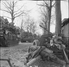 Churchill tanks laden with infantry of the 9th Durham Light Infantry pass a knocked-out German anti-tank gun as they enter Schilberg, 20 January 1945.
