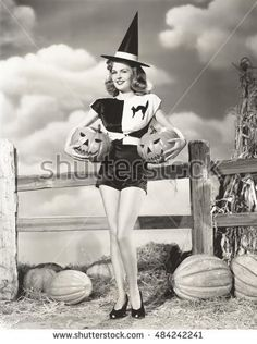 Bewitching woman carrying carved pumpkins