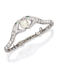 PLATINUM, DIAMOND AND EMERALD BRACELET- The opposing snakes centering an old mine-cut diamond weighing approximately 5.50 carats, accented by smaller old European and old mine-cut diamonds weighing approximately 6.45 carats, with two round emerald eyes, internal circumference 7 inches; circa 1925.