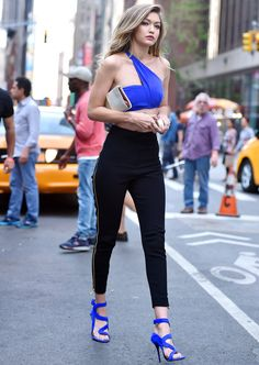 Gigi Hadid in a tiny blue asymmetrical crop top, showing off her toned midriff.