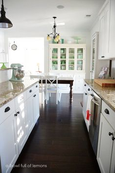 What a beautifully bright, airy and organized kitchen! Love the white with rich, dark floors! Via A Bowl Full of Lemons