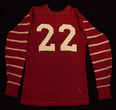 """Circa 1920's Football Jersey. This scarlet-hued wool pullover football jersey hails from the """"numbers-on-back"""" era, with """"22"""" sewn to the back in white felt-like numerals. There are nine white stripes adorning each long sleeve and a """"SPALDING"""" manufacturer's tag within the right front tail.  $1,086"""