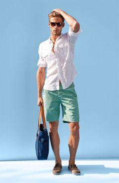 Pairing a white linen button-down shirt with pastel green shorts is a comfortable option for running errands in the city. Complement this look with brown suede boat shoes.