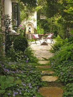 een padje naar een tafel set omgeven door veel planten en bloemen.