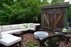 Inventive and eclectic patio. The patio is covered in a layer of recycled tree bark. Reclaimed wooden doors from Old Home Parts were flipped to show the more interesting, weathered side of the wood. The small roof is covered with a low-maintenance, lush garden from Live Roof.