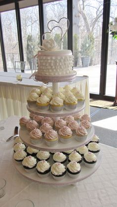 Wedding cupcake tower-really like the small wedding cake on top for bride and broom to cut. Each level  can be different flavor. I don't particularly like this one but cute idea for small wedding.