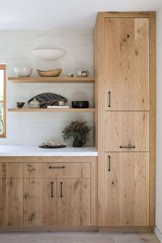 Blonde wood cabinets. White tile to the ceiling. Open shelving. Minimalist kitchen.