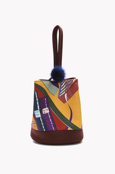 면 소재의 버킷백입니다. 프린팅이 들어간 디자인이며 가죽 소재의 스트랩에 링 후크와 폼폼 장식이 있습니다. 링 후크로 가방의 핸들을 조여서 고정가능합니다.