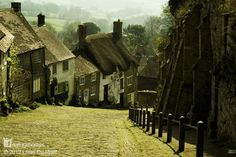 This is Gold Hill in Shaftesbury, England one of the beautiful ancient stone villages of Britain, some of them still loved and lived in since the mid-14th century. See more of them at www.naturalhomes.org/stonevillages.htm