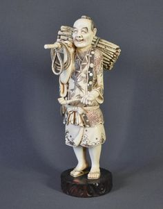 Large Japanese ivory figure. Man carrying a bundle of firewood and rope on shoulder, with pipe in left hand. on wooden stand which bears impressed seal with signature - Matsuyama (?). Height 32 cm (