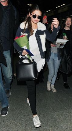 Selena Gomez stays comfy and chic when traveling in a shearling jacket, sweater tunic, and sneakers