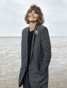 ELLE loves... tomboy model Arizona Muse wearing a long grey check blazer over a simple black top and trousers combination with a silver diamond brooch.