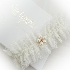 Filigree lace wedding garter with a rose gold and pearl flower