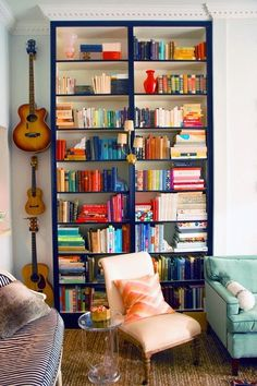 designmeetstyle:  A cozy corner doubles as an artful display and easy-access storage. Vibrantly colored books draw the eye, and a quirky sconce enlivens the space. The Lucite table is functional without leaving a cluttered appearance.