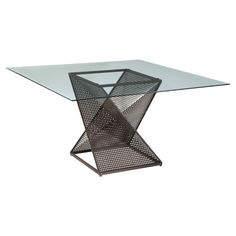 Serve family breakfasts and farm-fresh dinners at this contemporary-chic dining table, showcasing a geometric metal base with perforated details and a glass top.