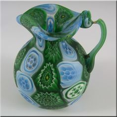 This is a magnificent 1920's/30's Venetian glass jug, made on the island of Murano, near Venice, Italy. There are no makers marks, but I strongly believe this piece was made by Fratelli Toso, similar items are shown in the book 'Italian Glass - Century 20' by Leslie Pina, page 84. Made up of loads of green, blue + white floral Millefiori murrine canes!
