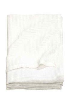 Narzuta w waflowy splot: Tkaninowa pojedyncza narzuta o waflowej strukturze z mieszanki zawierającej bawełnę.