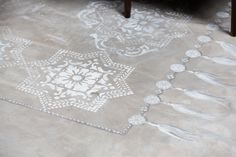 "Beautifully hand-painted ""rug"" on this concrete floor by @Caroline Lizarraga Decorative Artist using Royal Design Studio wall stencils (Lisboa Tile Stencil) on concrete floor."