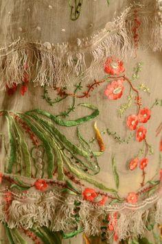 Robe vers 1920, en mousseline jaune et gaze crème à décor japonisant de feuillage et fleurs de pruniers à dominante de vert et de rose. Haut sans manches à col pèlerine, jupe à 4 volants festonnés, frangés deffilé et sourcils de hanneton, (bel état malgré quelques trous). Réemploi probable de létoffe dune robe du Second-Empire.