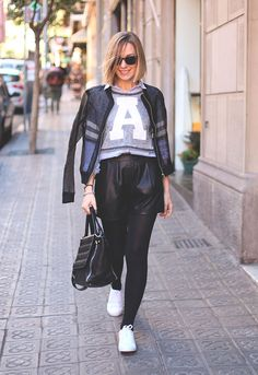 Street style look jaqueta de couro, moletom cinza, shorts couro e tênis branco.