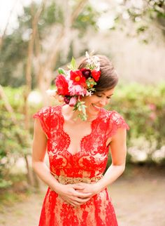 Red lace wedding dress and vibrant hair flowers. #red #bridal #fashion