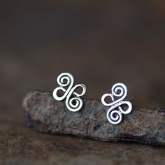 Small stud earrings in a shape of double spiral knot inspired by Celtic artwork. These knot shapes are completely unisex, suitable for both men and women. - Shapes measure approx 11mm x 9mm - Earrings