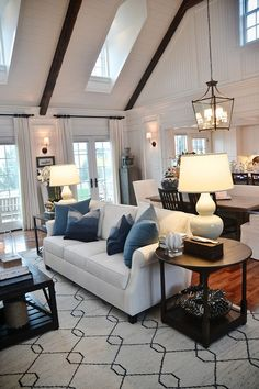 Cozy neutral living room with high ceilings & pops of blue.