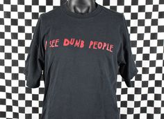 Vintage 90s I See Dumb People funny t-shirt!  Condition: Great vintage condition with fading and other normal wear throughout! Check out the pictures!  Tag: Delta  Era: 90s  Fabric: 100% Cotton **Vintage tshirt sizes may be different than contemporary shirt sizes so please check the measurements.**  Tag Size: XL  Chest (pit to pit): 23  Length (top of the shoulder to bottom hem on front): 29  Vintage tshirts are usually 15-30 years or older and may show wear consistent with their age. Please…