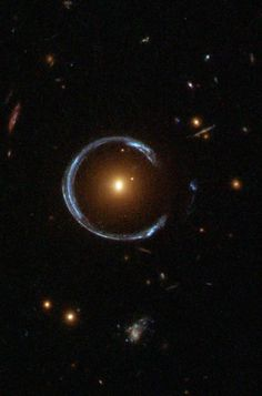 "An ""Einstein Ring""or gravitational lensing at work: the blue galaxy is behind the yellow galaxy but we can see it because the light from the far galaxy gets wrapped around by the closer galaxy. Photo NASA/Hubble"