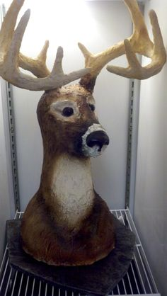 Meet Buck! - Buck is just that...a 10 point buck.  I've included pictures of the structure to help people see how he was built.  If I do another one of these, I will also drill holes next to the antlers for ears as they did NOT make it to the event and threatened to ruin the entire cake.  He was made with red velvet cake- 12, 10, 9, 8, and 6 inch single layers.  The top of the neck and head were RKT.  All airbrushed buttercream (hair texture by brushing set buttercream with dampened pastry b...